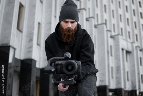 Fototapeta Bearded Professional videographer in black hoodie holding professional camera on 3-axis gimbal stabilizer