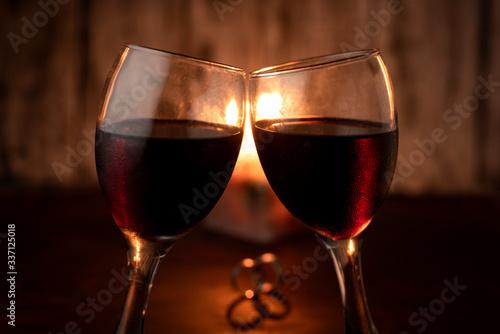 Photo dos copas de vino celebrando con dos anillos en una mesa calida a la luz de la v