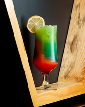 A Glass Of Ombre Cocktail With Green And Orange Colors Topped With Lemon