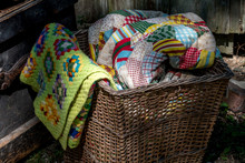 Old Wicker Basket Filled With Hand Made Quilts And Blankets