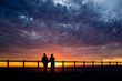 Couple Standing Against Cloudy Sky During Sunset