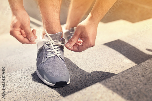 Young man tying shoelaces on his sneakers outdoors on sunny day, closeup Tableau sur Toile