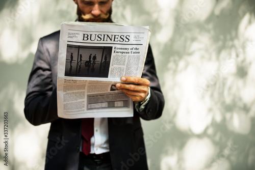 Obraz na płótnie Businessman standing and reading newspaper