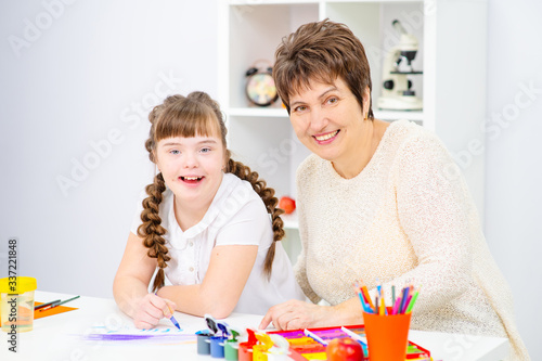 The girl and mother sitting at the table draw a picture at home Fototapete
