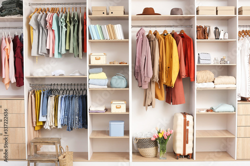 Fototapeta Big wardrobe with different clothes and accessories in dressing room