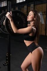 Fototapeta na wymiar Young girl training in a gym profile view