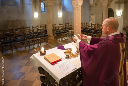 Leinwand Poster Priester feiert Messe ohne Gläubige