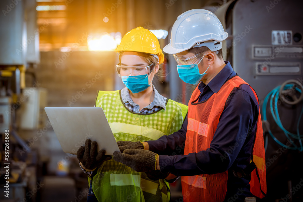 Fototapeta Portrait woman worker under inspection and checking production process on factory station by wearing safety mask to protect for pollution and virus in factory.