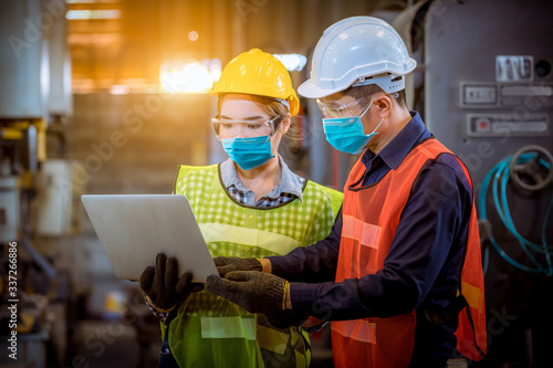 Obraz na plátně Portrait woman worker under inspection and checking production process on factory station by wearing safety mask to protect for pollution and virus in factory