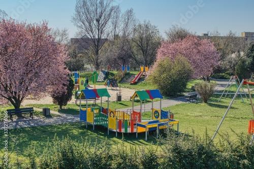 Fototapeta pusty plac zabaw dla dzieci podczas pandemii, zakaz poruszania się podczas pandemii, kwitnące kolorowe krzaki, przyrządy do zabaw i ćwiczeń obraz