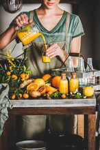 Immune Boosting Vitamin Health Defending Drink. Young Woman Pouring Fresh Turmeric, Ginger, Citrus Juice Shot From Jug To Bottle In Kitchen. Pure Vegan Immunity System Booster