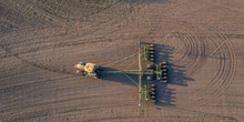 Spring Field Work, A Tractor With A Mounted Seeder Sow Seeds In The Ground On An Agricultural Field. Aerial Video
