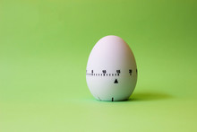 White Egg Timer On Green Background. Happy Easter In The Kitchen. Home Related, Home Staying. Free Copy Space.