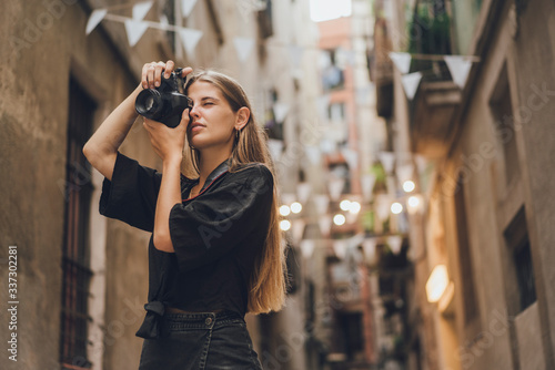 Female tourist photographer is trying to catch the moment, she picked up her photo camera, pressed it to her face and started to take pictures. She is smiling and enjoying the streets of the city