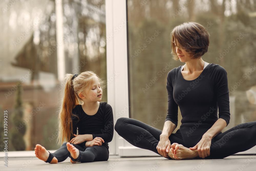 Fototapeta Girl is engaged in gymnastics. Family in a yoga studio. Kid in a black sportwear.