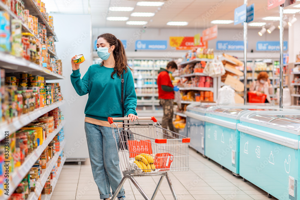Fototapeta Shopping trip. A young, pretty Caucasian woman with a medical mask on her face reads ingredients on a tin can. Product purchase concept and the coronovirus pandemic