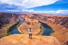 Young Tourist Man Standing Horseshoe Bend With The Colorado River In The Background