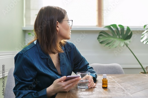 Female in pajamas sitting at home, drinking water with medicine, reading smartph Canvas Print
