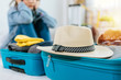 Leinwanddruck Bild - focus vintage hat on suitcase with woman hipster traveler sad after flight cancelled with packing clothes into suitcase for vacation at home, delayed flight, summer holiday, backpacker, travel concept