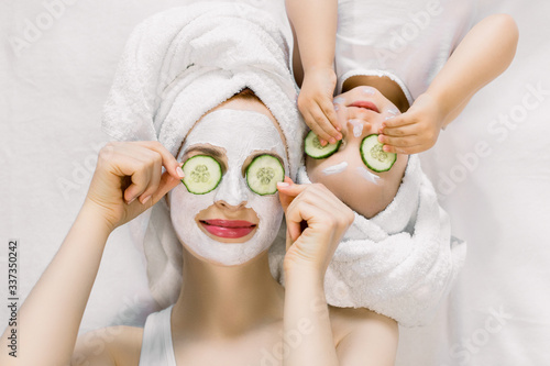 Fototapety, obrazy: Mom and her 2 years old baby girl having fun together, making clay facial mask and cucumber slices on eyes. Mother with child doing beauty treatment together. Family time, spa and beauty, mothers day
