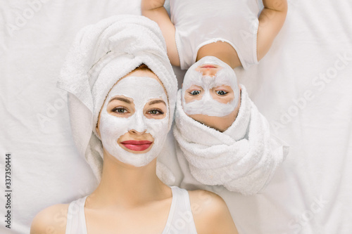 Fototapety, obrazy: Portrait of pleasant young mother and her little daughter lying together on bed with white towels on head and facial clay mask while enjoying spa procedures. Isolated, top view. Beauty concept