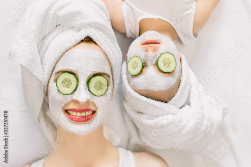 Fototapety, obrazy: Mother and daughter doing funny spa procedures after bath. They are in white bath towels with white facial mud mask on faces and slices of fresh cucumber on their eyes. Family spa, mothers day