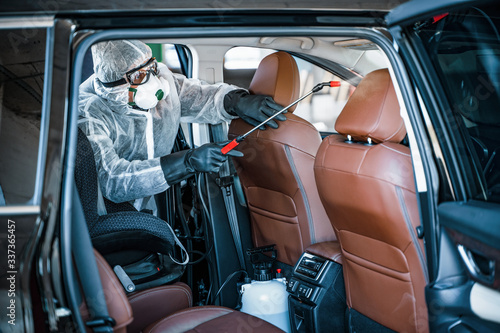 Obraz Disinfectant worker in protective mask and suit making disinfection of car seats - fototapety do salonu