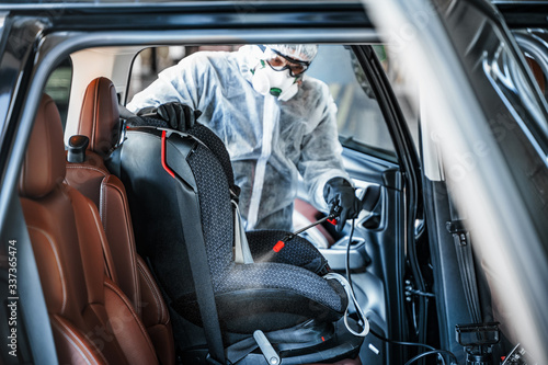 Obraz Disinfectant worker in protective mask and suit making disinfection of baby car seat - fototapety do salonu