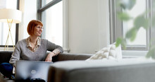 Woman With Laptop Sitting On Sofa At Home