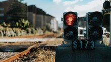 Piece Of Equipment Shining A Red Light Next To The Train Tracks