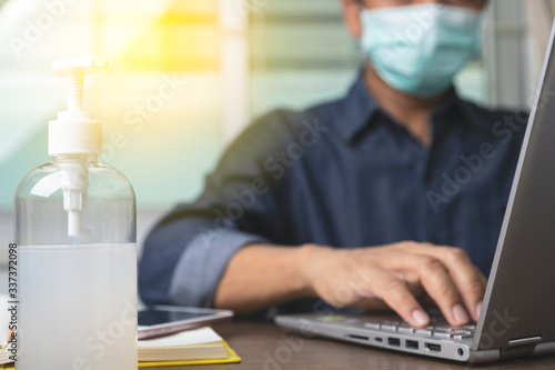 Obraz Alcohol gel with male employee wearing a health mask Preventing corona virus infection covid-19 in back, concept of working from home and social distancing. - fototapety do salonu