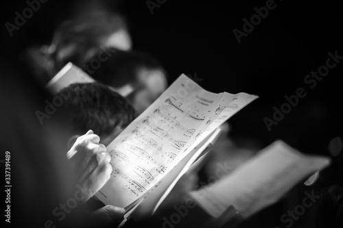 Photo Hand holding music score in choir