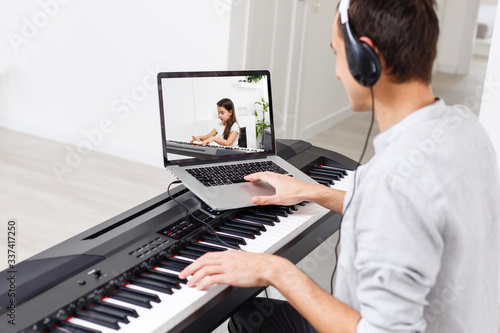 A man learning to play piano online with a computer staying at home Canvas Print