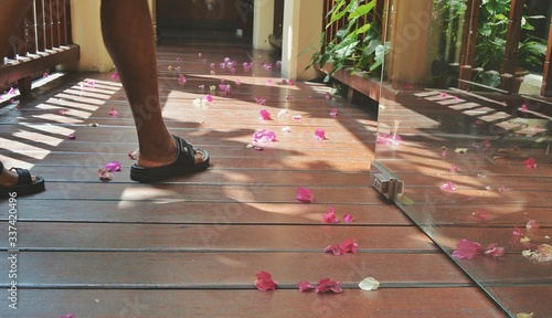 Obraz Low Section Of Man Standing By Pink Petals On Floor - fototapety do salonu