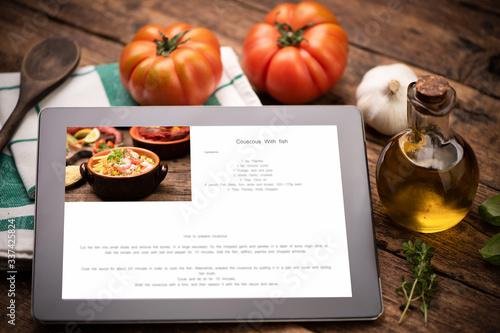 Food recipes tablet computer on rustic wooden table Fototapeta