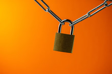 Padlock Connecting A Metal Chain On An Orange Background. Web Banner.