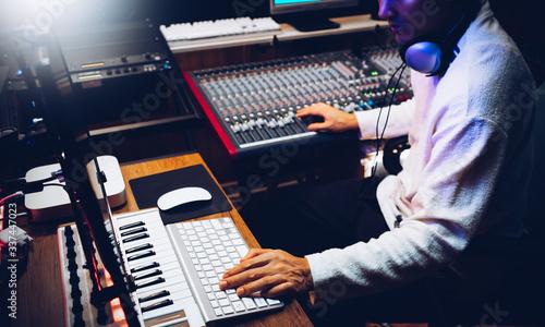 Fotografía male music producer, composer arranging a song in home recording studio