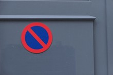 Close-up Of No Parking Sign On Gray Wall
