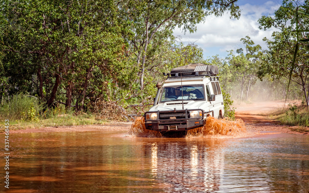 Fototapeta Western Australia – Flooded Outback gravel road with 4WD car crossing the waterhole with splashing muddy water at the savanna
