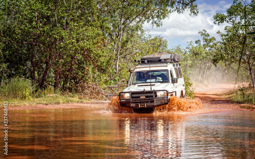 Obraz Western Australia – Flooded Outback gravel road with 4WD car crossing the waterhole with splashing muddy water at the savanna - fototapety do salonu