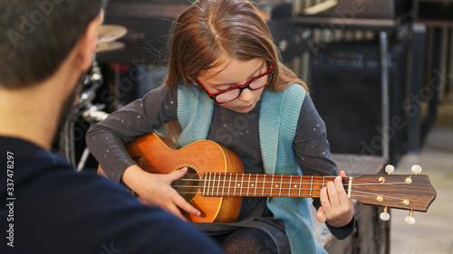 Fototapeta Dad teaching guitar and ukulele to his daughter
