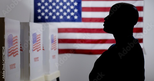 MS silhouetted African American man looking at voting booths, with hand over hea Tablou Canvas