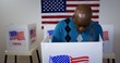 Leinwandbild Motiv MS front view African American man in blue sweater and wearing a silver cross on a chain casting vote in booth at polling station. US flag on wall in background