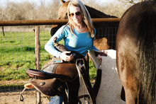 Western Lifestyle Shows Woman Carrying Saddle Beside Horse On Farm.
