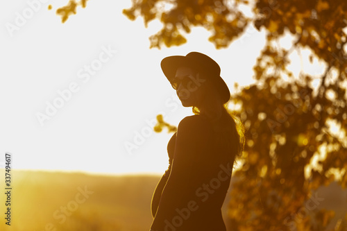 Fototapeta Beautiful pregnant woman in hat and sunglasses outside on warm sunny day. Facing to sun, looks at camera. Summer nature backsides. Yellow tones. Rest in park, meditation, retreat concept obraz na płótnie