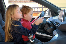Brother And Sister Are Holding The Steering Wheel Of A Car. A Girl Of 8 Years Old And A Boy Of 4 Years Old Play Simulate The Process Of Driving A Car, Side View. Children Sharing Time Concept