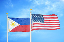 Philippines And United States Two Flags On Flagpoles And Blue Cloudy Sky