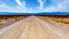 A Long And Straight Gravel Road In The Semi Desert Landscape Near Crystal Springs And Area 51 In The Desolate Land Of The Nevada Desert In The United States
