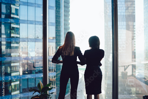 Obraz na plátně Back view of female colleagues in formal wear standing near window looking at mo