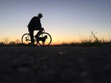 Side View Of Silhouette Man Sitting By Bicycle On Landscape Against Sky